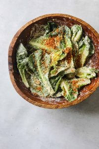 a wooden salad bowl filled with romaine lettuce tossed with Creamy Tahini Caesar Dressing