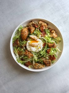 a white bowl filled with Frisée Salad with Bacon, Croutons, and Poached Egg