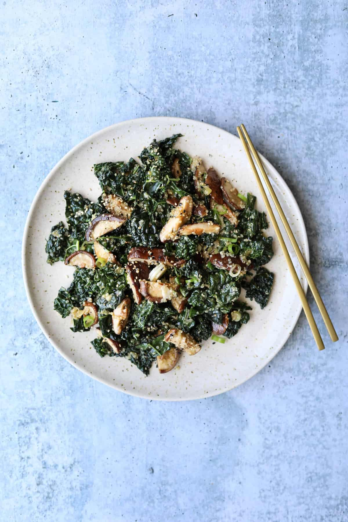 Kale and Quinoa Salad with Shiitake Mushrooms on a plate with gold chopsticks