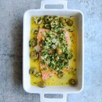 Slow Roasted Salmon in a baking dish with topped with green olive salsa verde