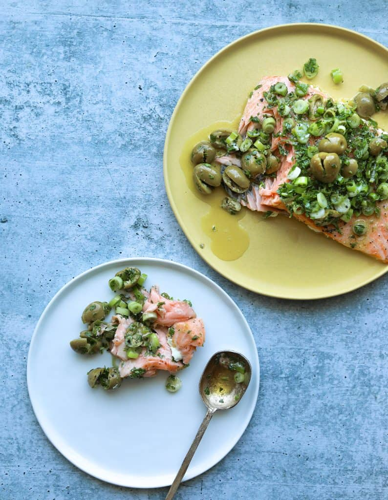 Slow-Roasted Salmon with Green Olive Salsa Verde served on a platter with a gold spoon