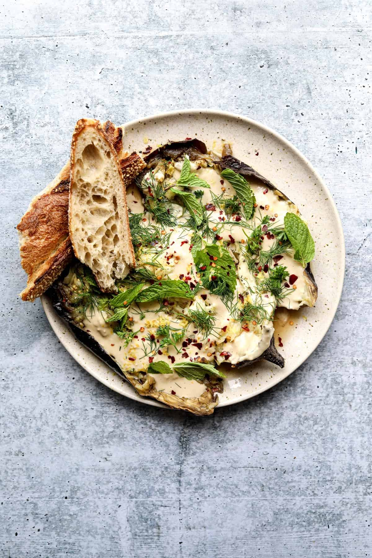 Whole Roasted Eggplant with Garlic Tahini on a plate with toasted bread