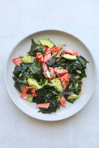 kale salad on a plate with salmon, avocado and sesame seeds