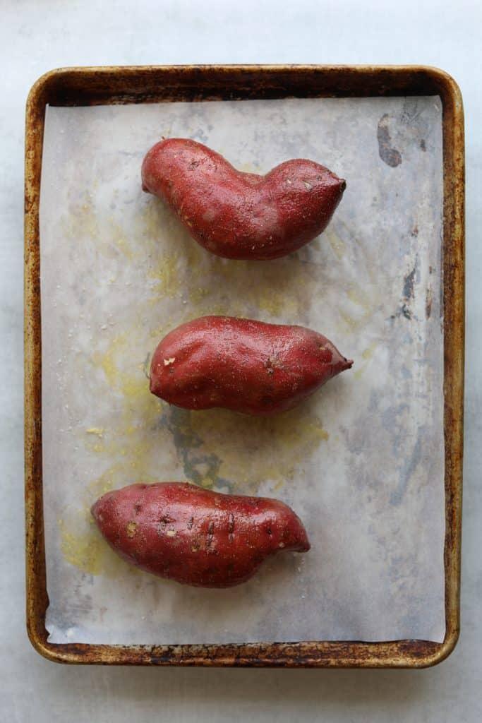 three sweet potatoes on a tray ready for roasting