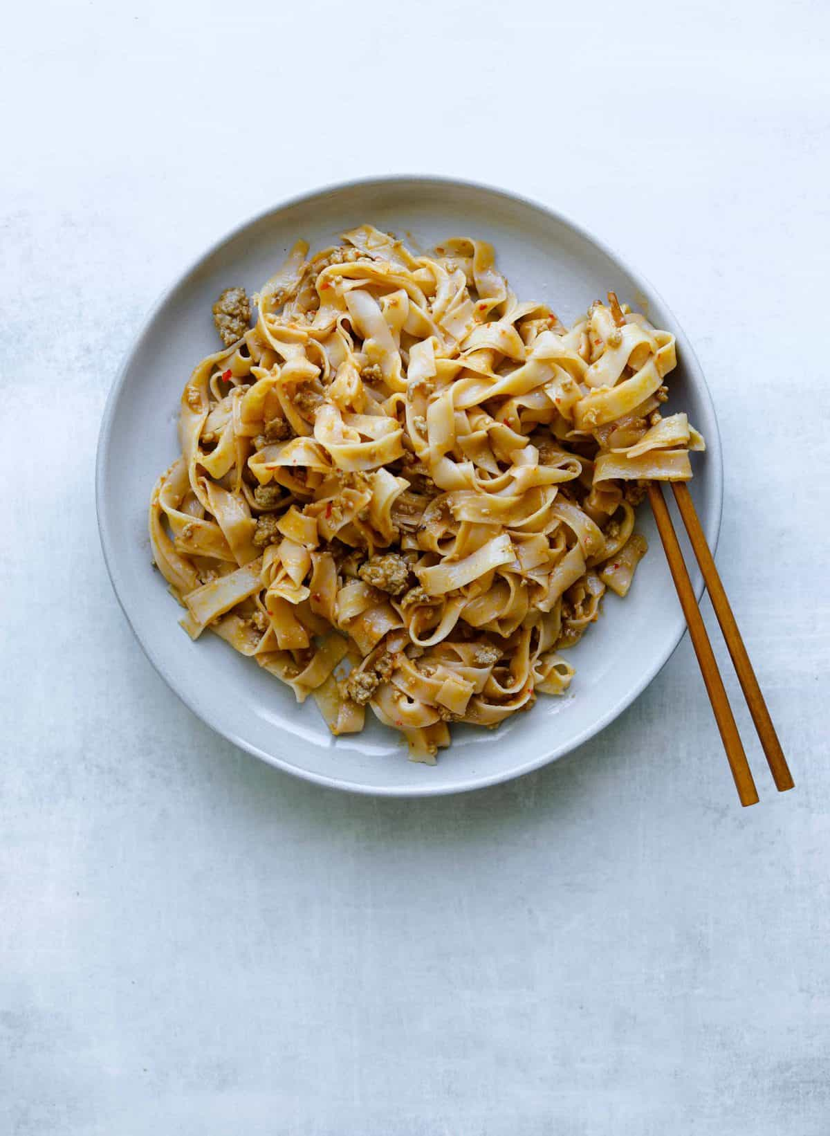 rice noodles on a plate with peanut and pork sauce