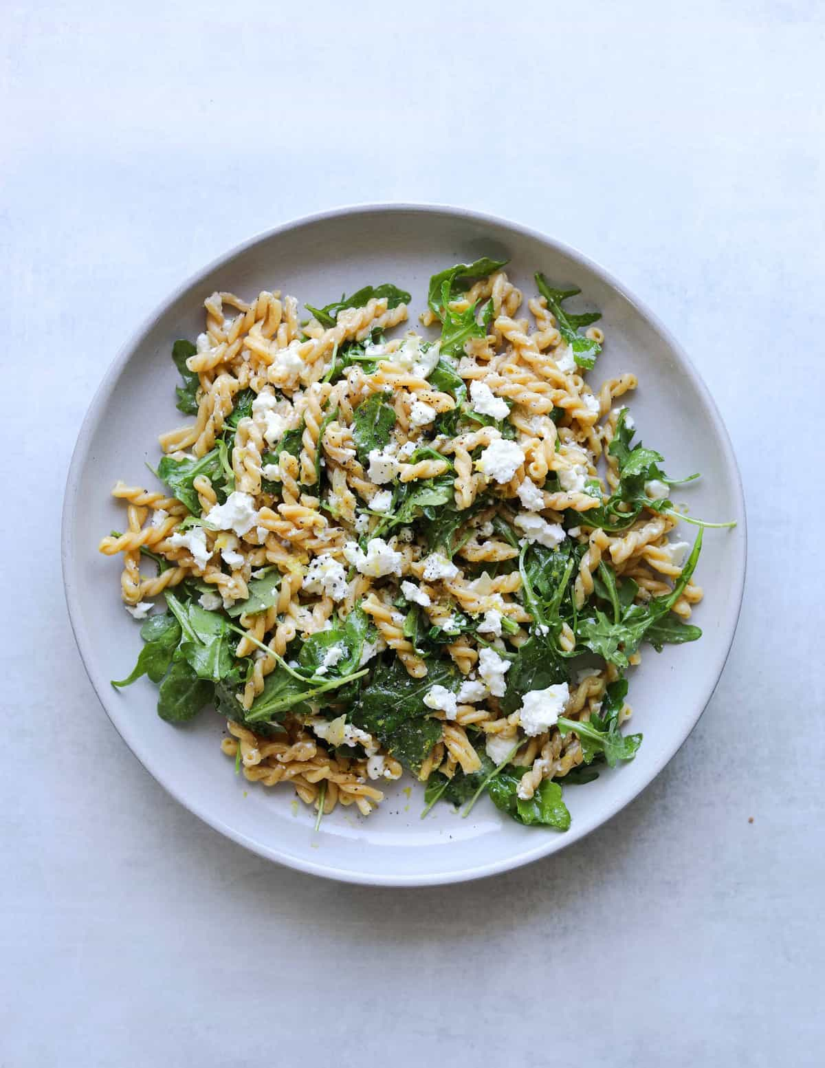 chickepea pasta with arugula and feta on a white plate