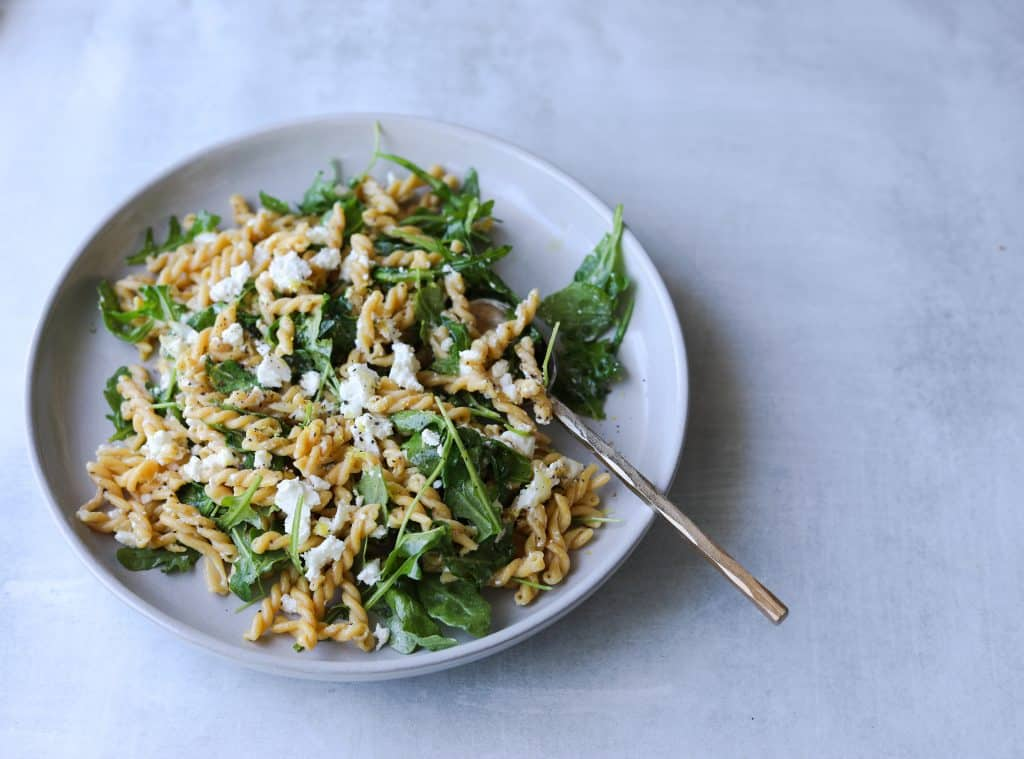chickpea pasta on a plate with arugula, feta and a gold serving spoon