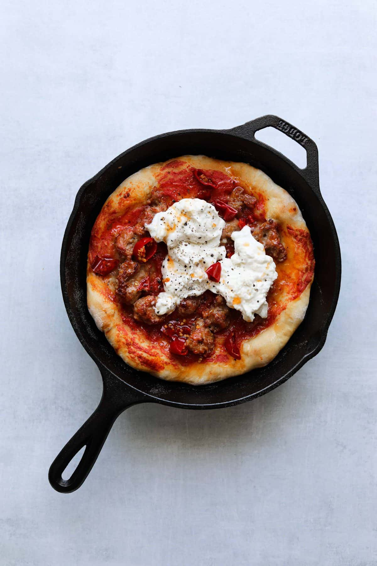 pizza in a cast iron pan topped with sausage, chilis and burrata