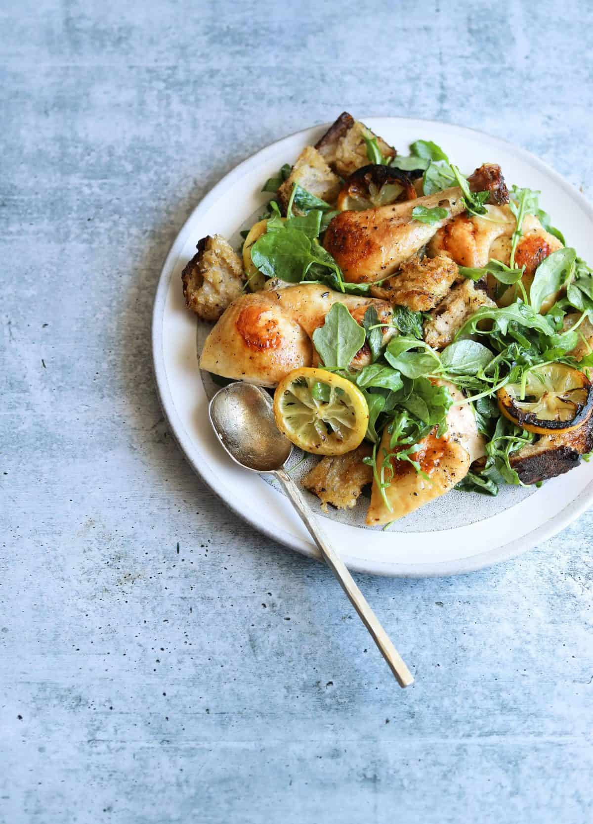 Roast Chicken with Toasted Bread Salad on a white plate with a gold spoon