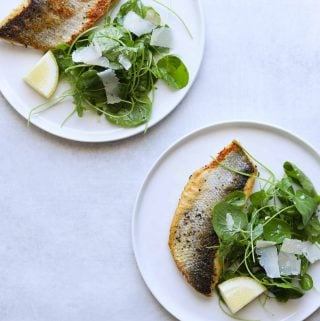 two plates with a filet of crispy skin branzino and watercress salad