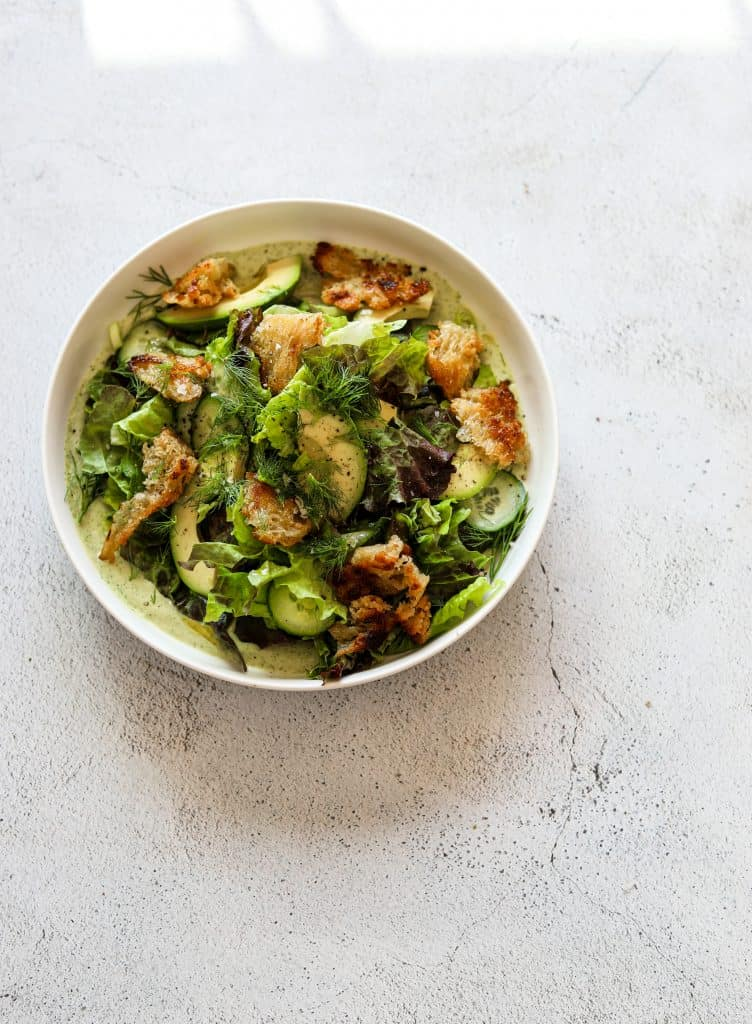 Green Goddess Salad with Basil-Tahini Dressing in a white bowl