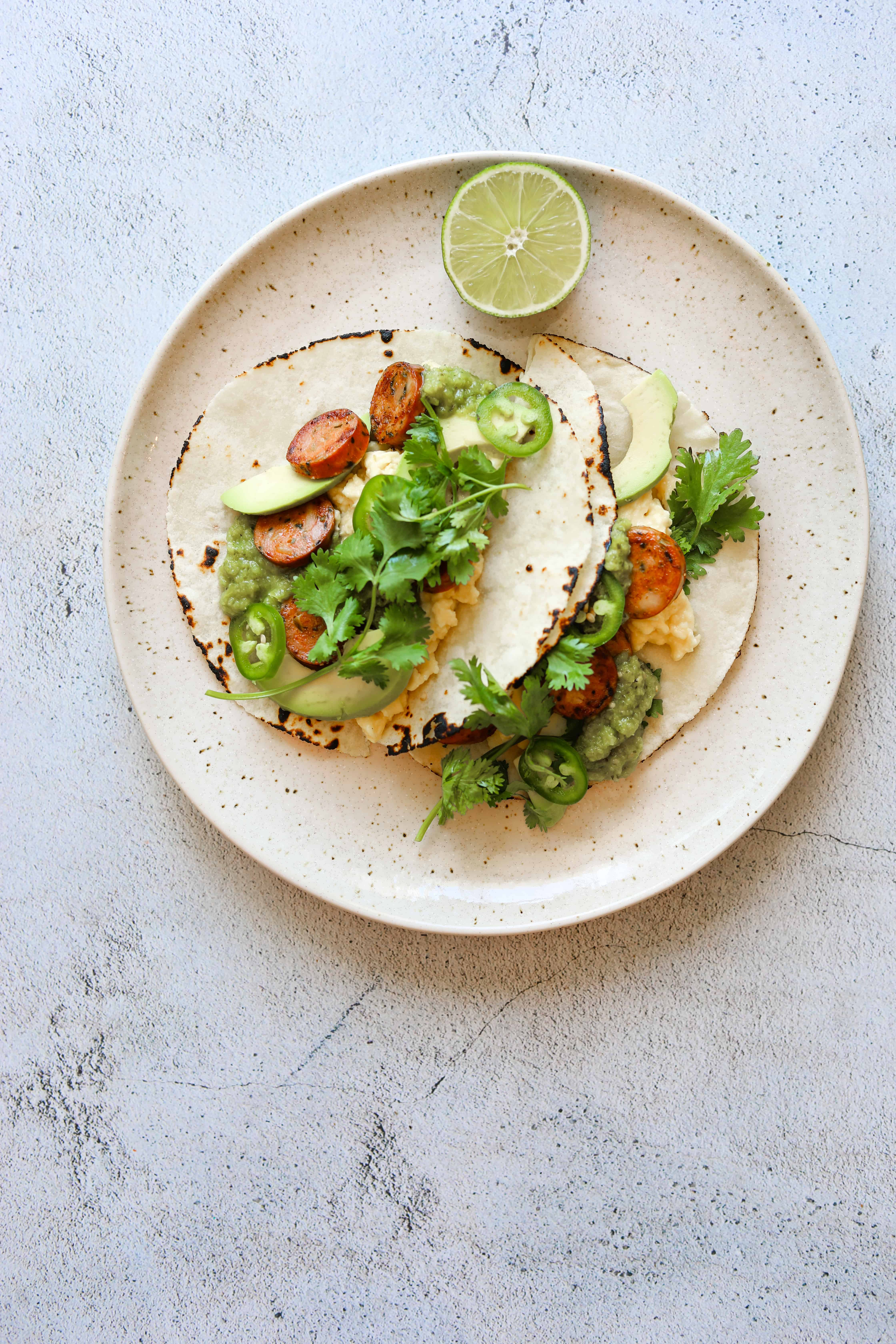 Paleo Breakfast Tacos on a plate with a slice of lime