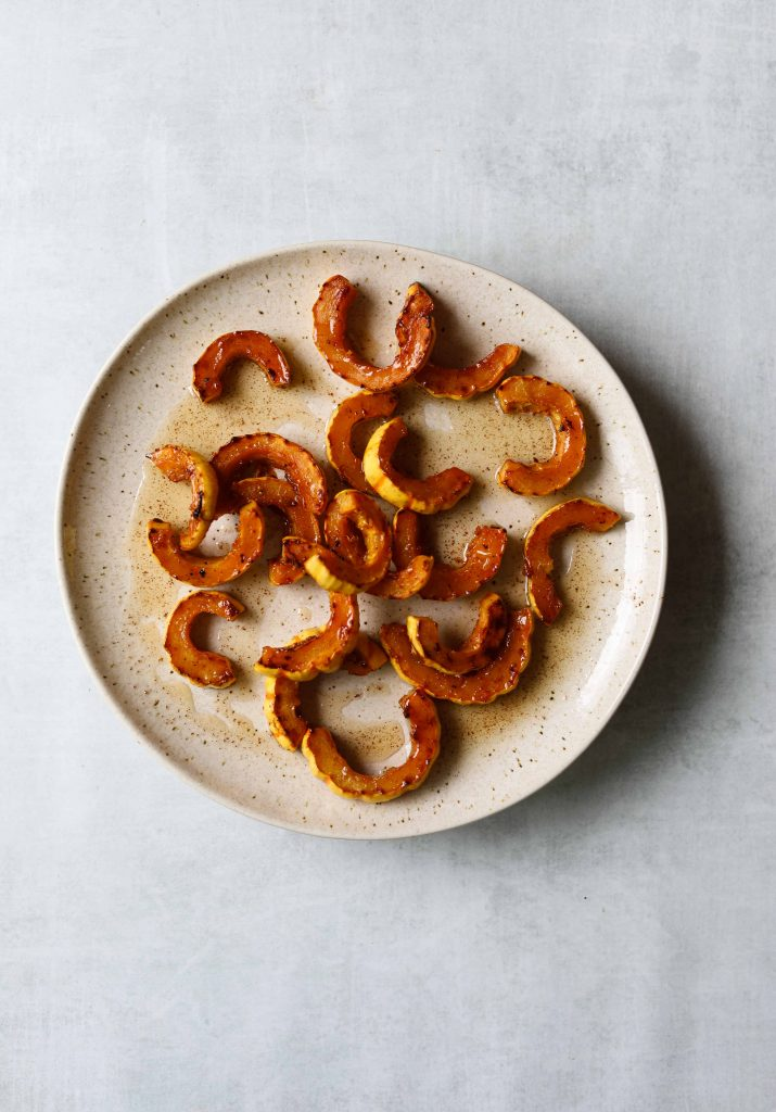 Maple- brown butter roasted squash on a white plate