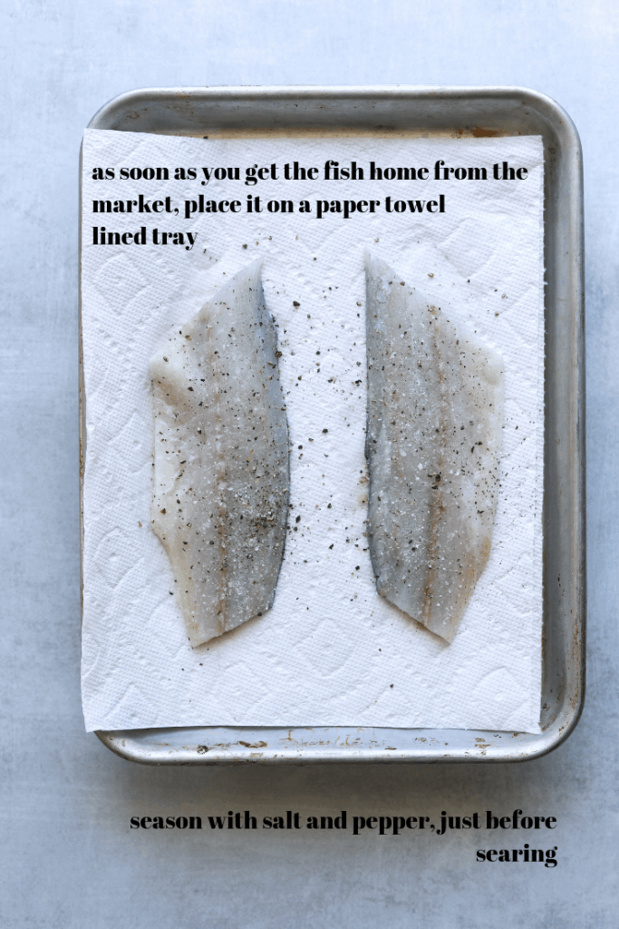 raw branzino on a sheet tray seasoned with salt and pepper