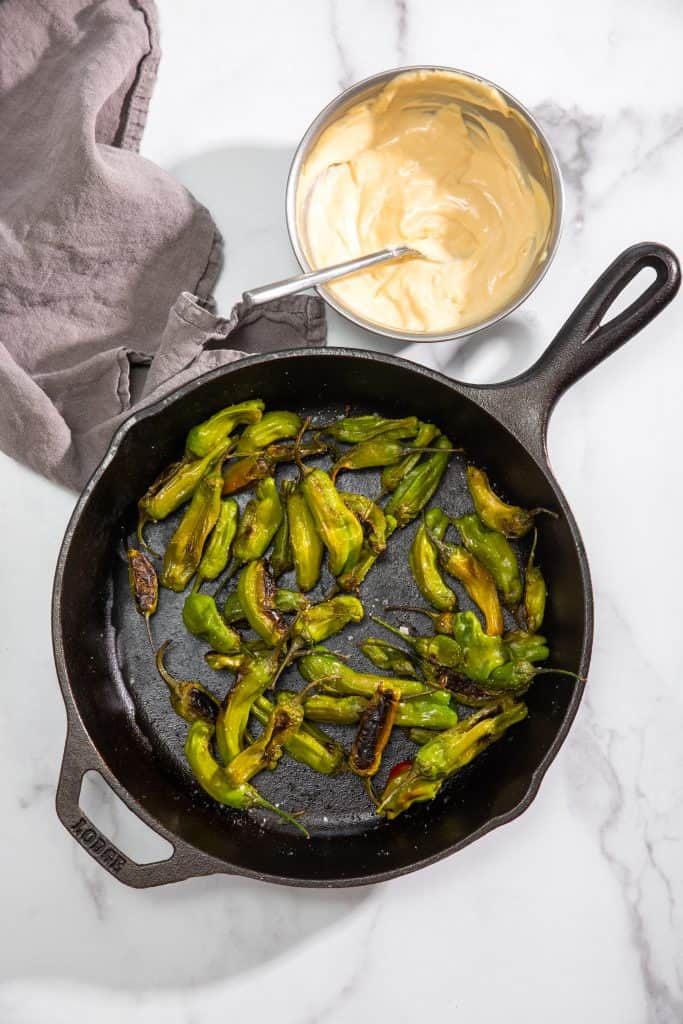 shishito peppers in a cast iron pan with soy-garlic mayo on the side