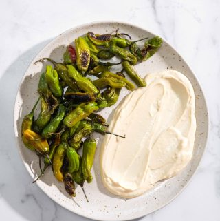 blistered shishito peppers on a plate with soy-garlic mayo