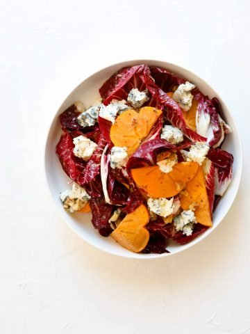 Persimmon and Blue Cheese Salad with Grainy Mustard Vinaigrette in a bowl