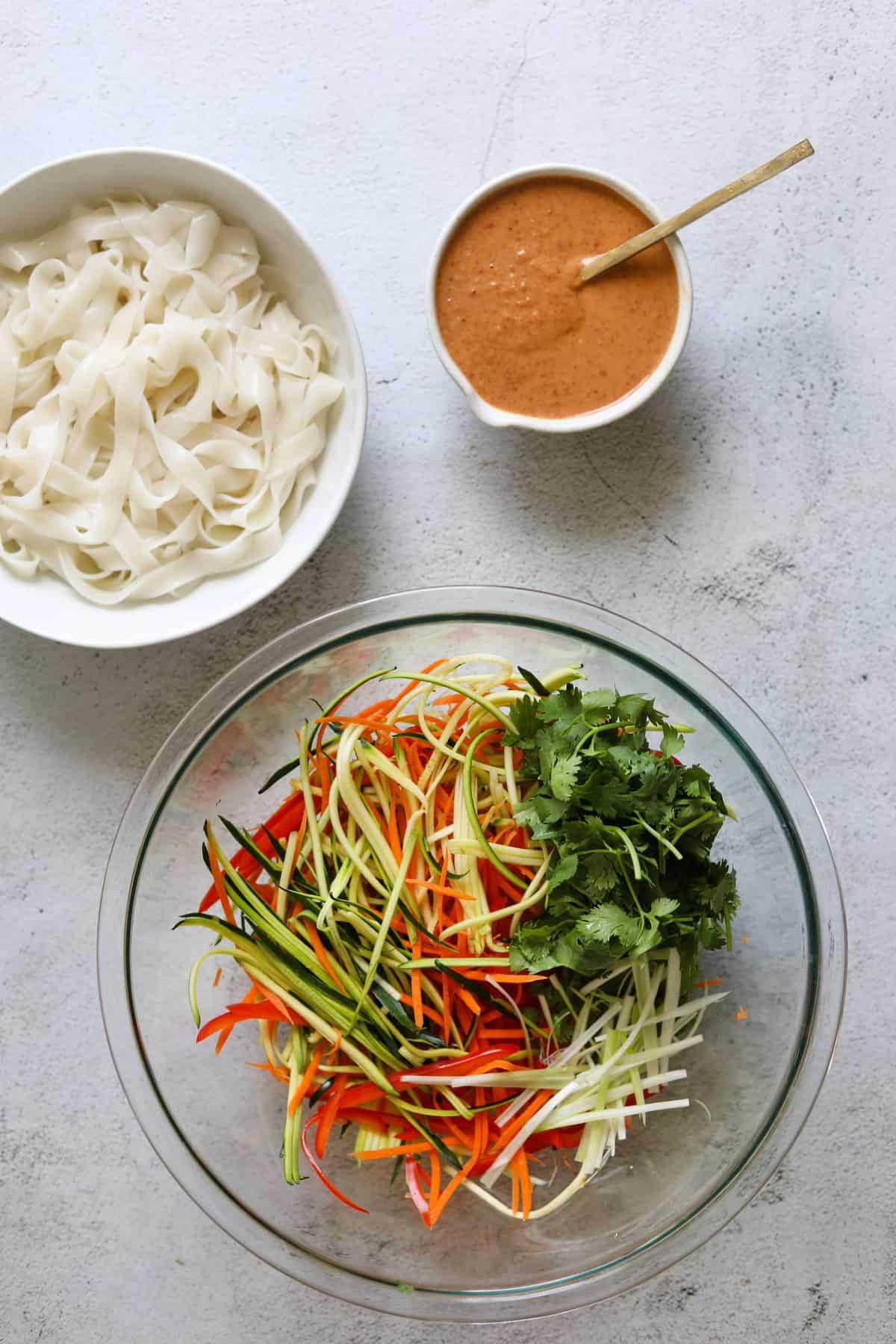 Creamy Coconut Thai Noodle Salad ingredients in a bowl with the sauce on the side
