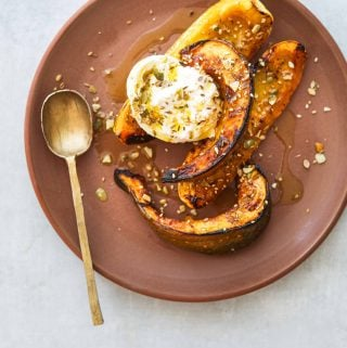 Honey Roasted Squash with Burrata and Pumpkin Seed Dukkah on a brown plate with a gold spoon