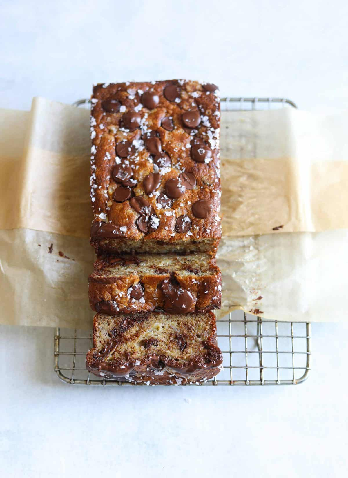 a loaf of Salted Dark Chocolate Banana Bread on a brown parchment lined baking rack