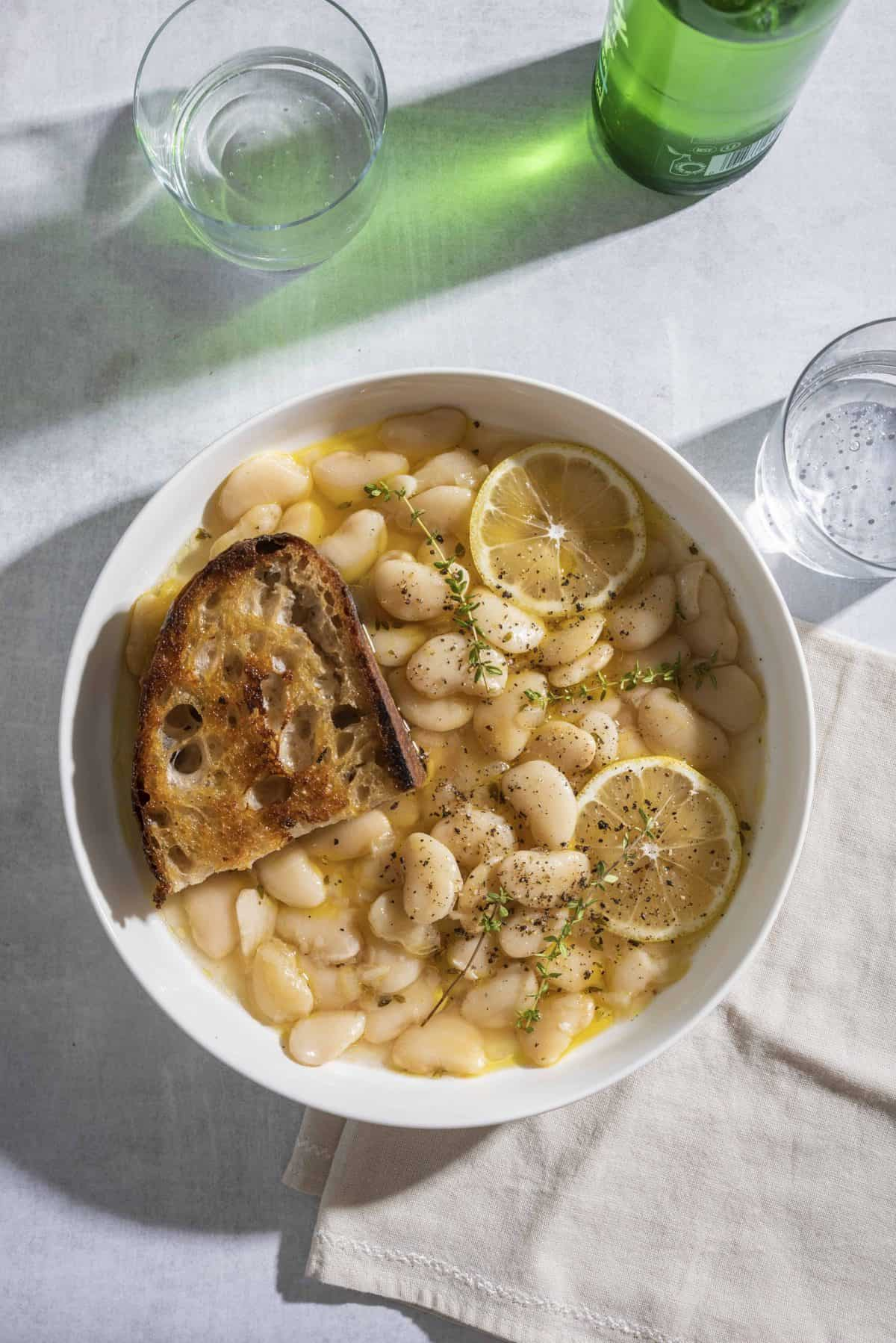 Brothy White Beans with Parmesan + Lemon in a white bowl