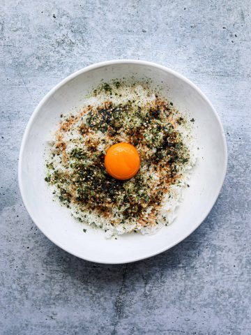 a white bowl with rice, furikake seasoning and an egg yolk