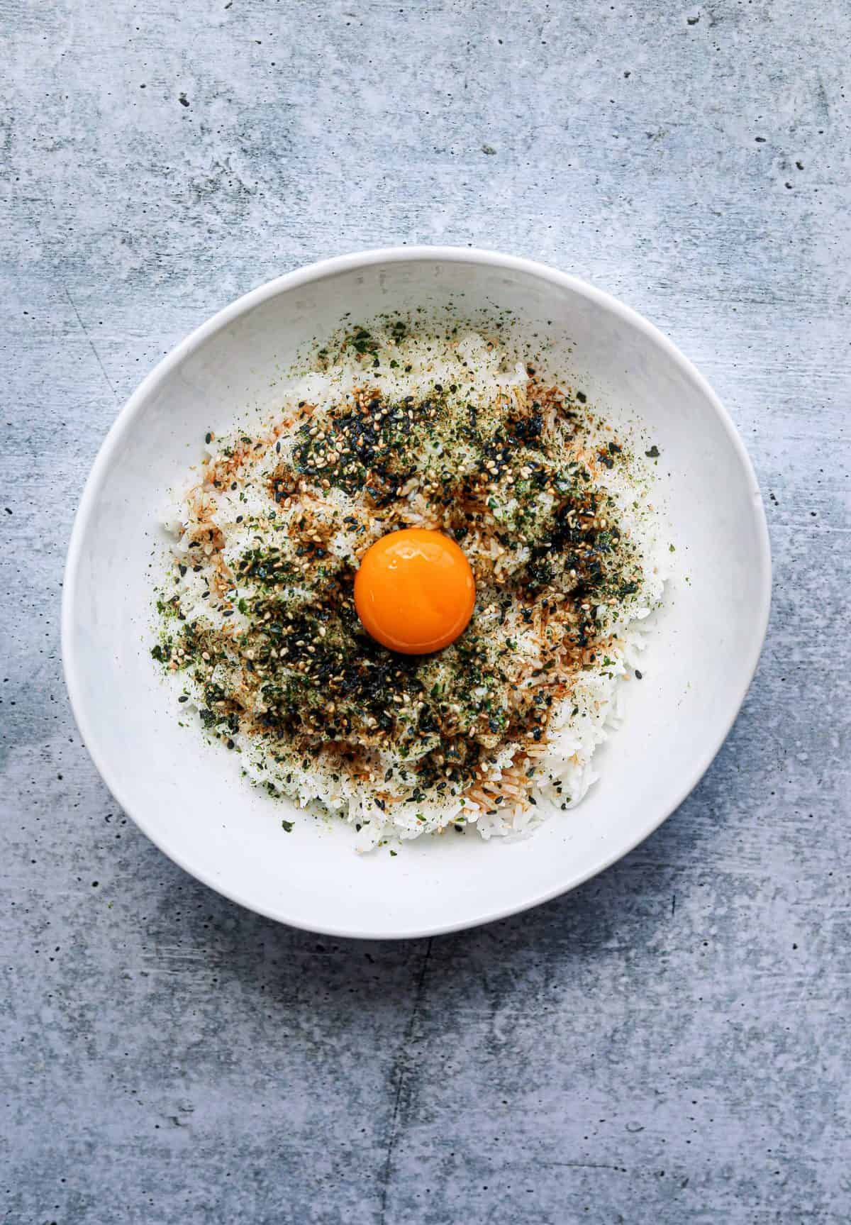 a white bowl with rice, furikake seasoning and an egg yolk