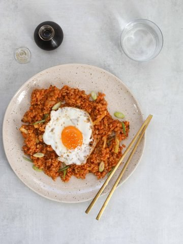 Kimchi Brown Rice Breakfast Bowl on a Blue Background