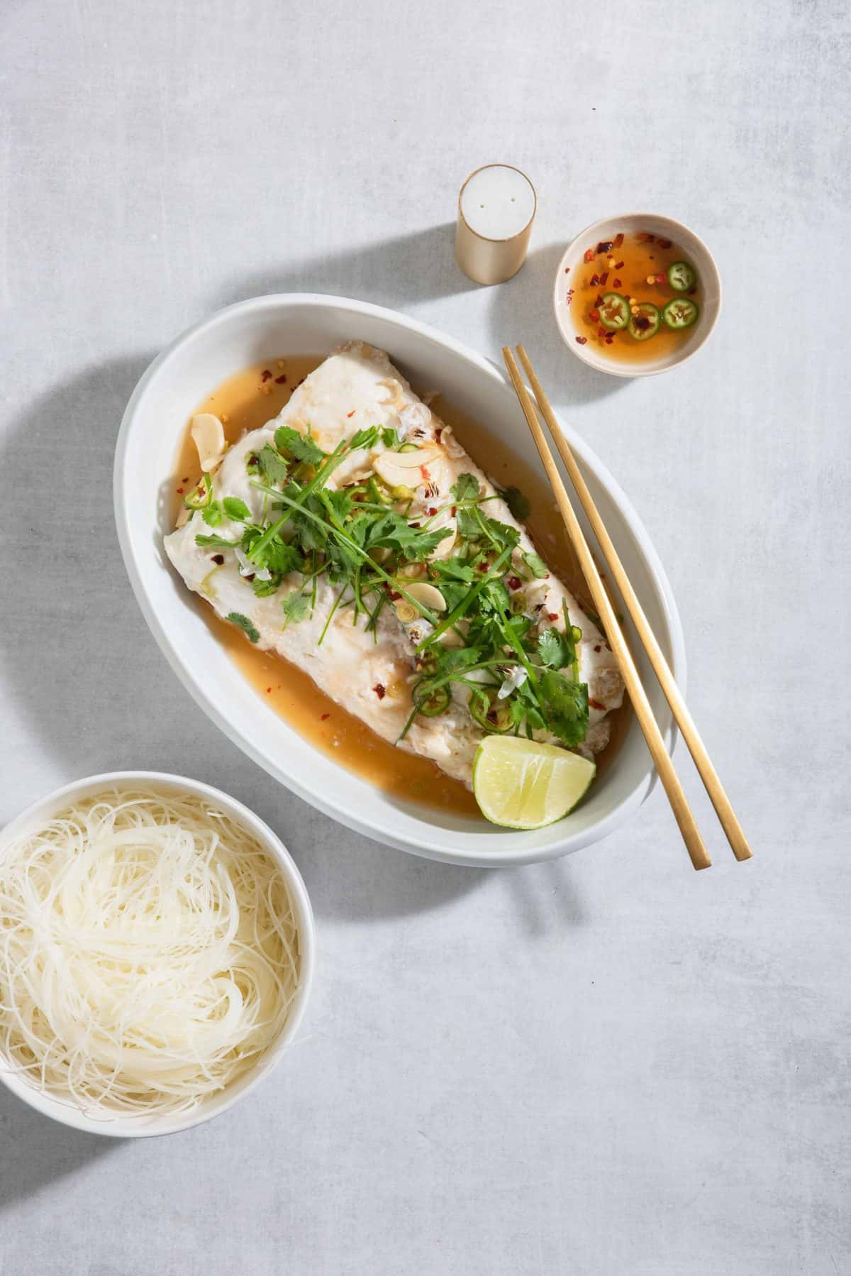 Steamed Halibu in a white serving dish with garlic-lime sauce and rice noodles