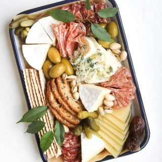 A charcuterie and cheese platter on a rectangular tray