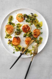six seared scallops on a plate drizzled with preserved lemon and herb dressing