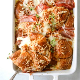 Croque Monsieur Croissant Bake in a white baking dish with a silver spoon