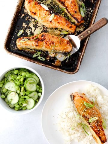 A sheet pan with salmon filets, a bowl of edamame salad and a bowls of rice with miso-honey salmon on top.