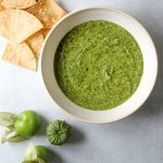 Tomatillo Salsa in a white bowl with tortilla chips and tomatillos