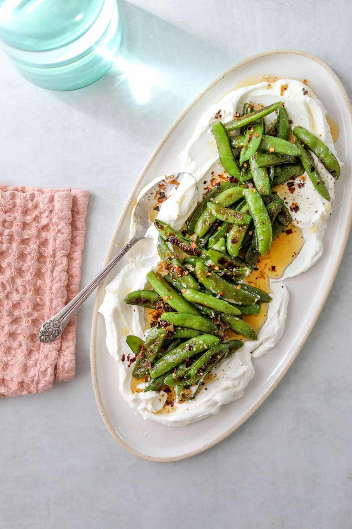 a platter with Roasted Snap Peas with Yogurt and Garlic Chili Oil