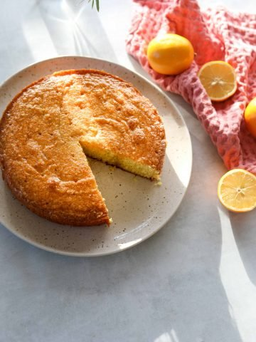 Meyer lemon polenta cake with a slice missing sitting on a cream plate surrounded by lemons and a pink tea towel