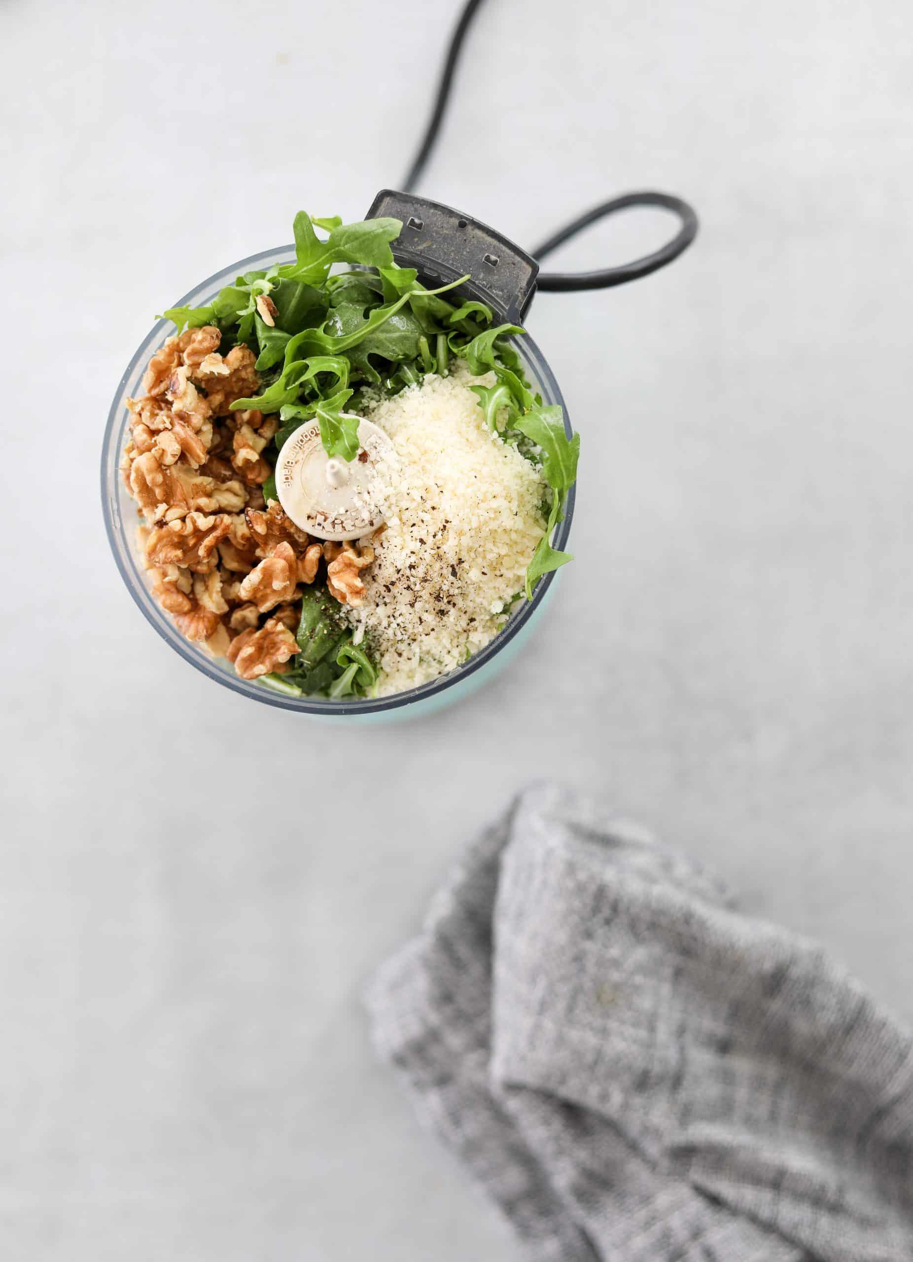 Arugula pesto ingredients in a food processor.