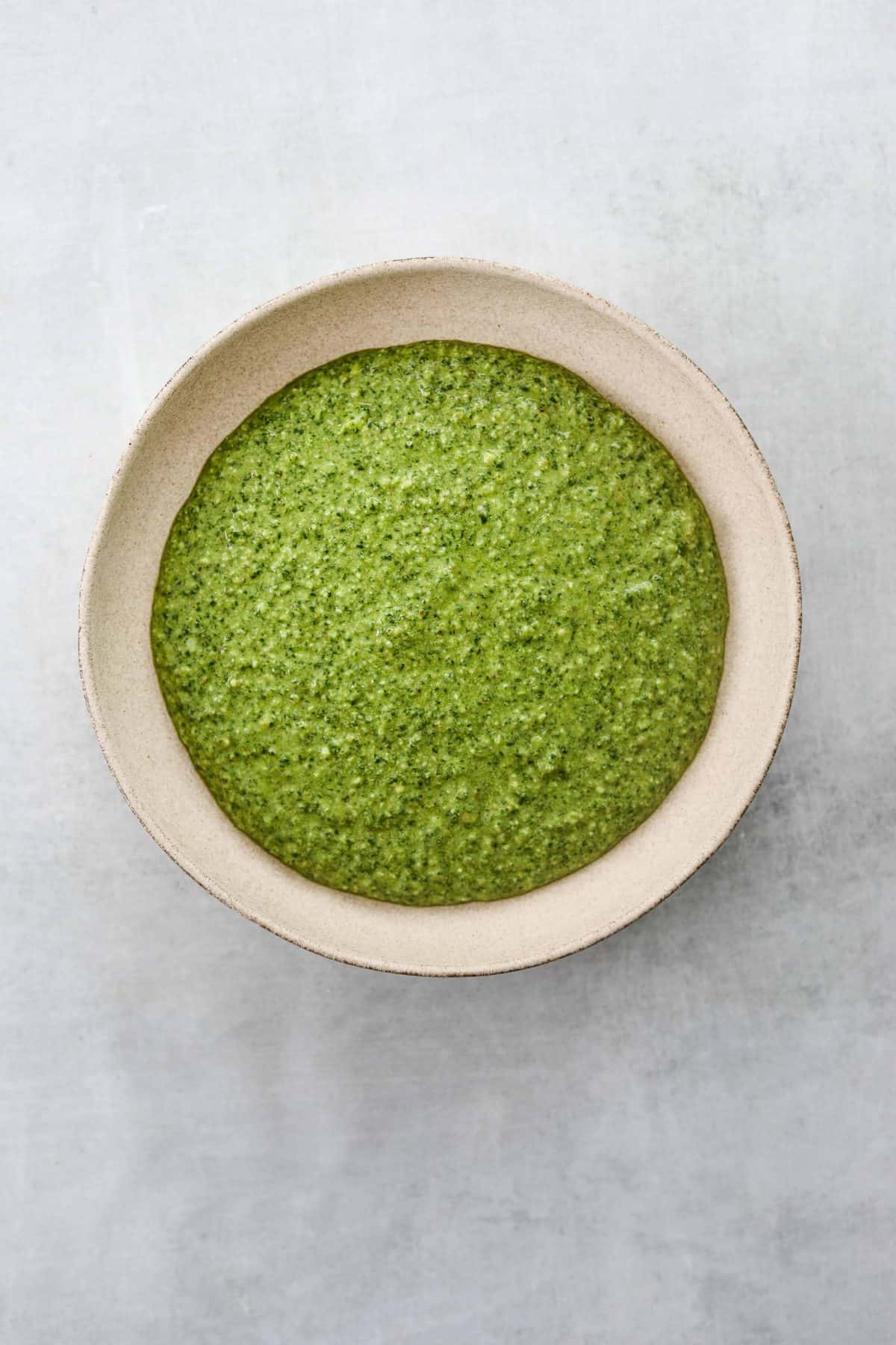 a bowl of bright green Arugula and Walnut Pesto