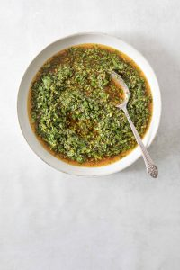 Chimichurri in a bowl with a silver spoon