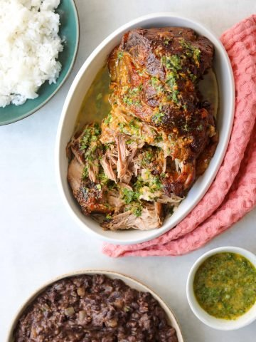 tender roasted pork in an oval baking dish with side dishes of rice, beans and mojo sauce