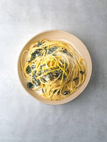 a white bowl filled with Bucatini al Limone with Wilted Kale