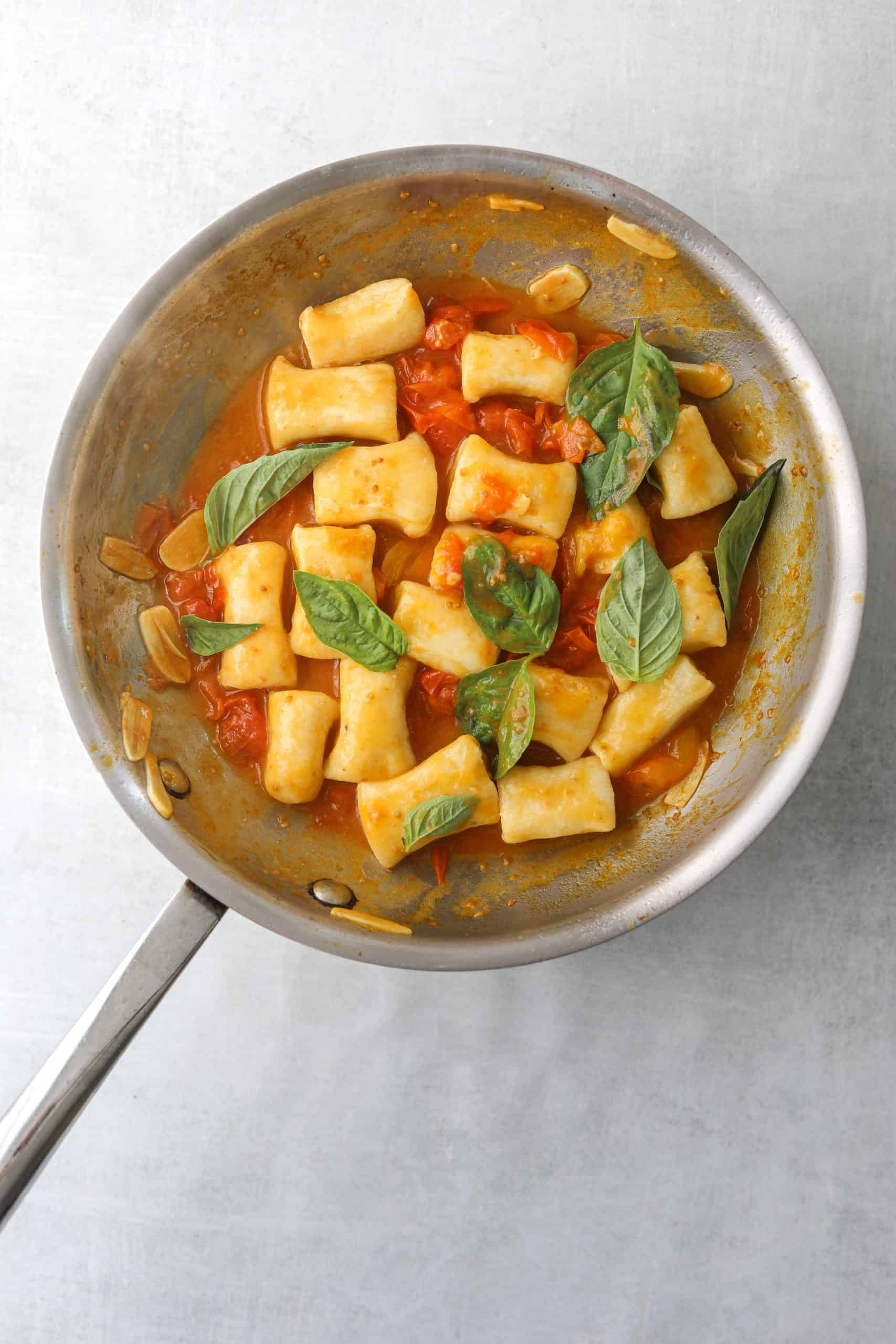 a saute pan filled with ricotta gnocchi, cherry tomato sauce, sliced garlic and fresh basil
