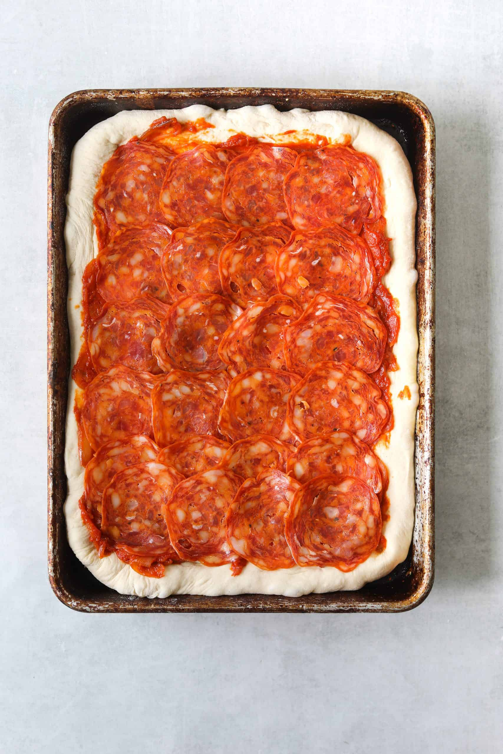 an uncooked rectangle pizza on a sheet pan topped with soppressata
