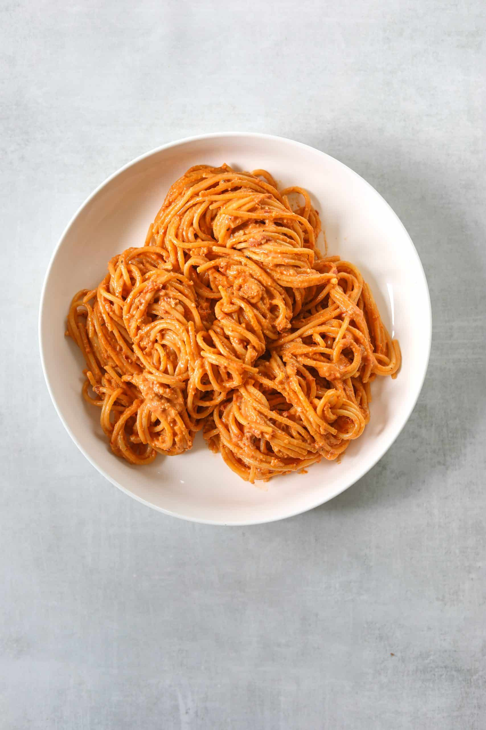 a white bowl filled with pasta on a blue background