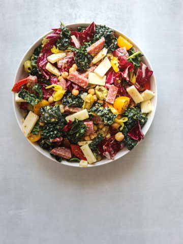 a white bowl of california chopped salad with provalone cheese, kale, tomatoes and salami on a blue background