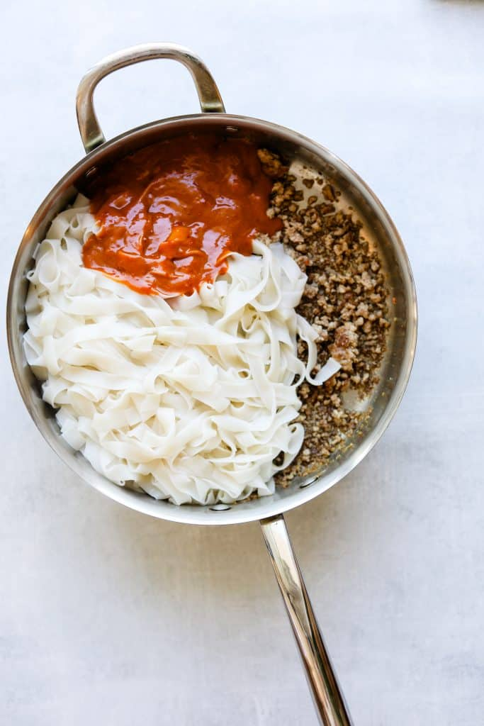 ground pork, spicy peanut sauce and rice noodles in a pan