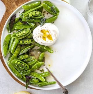 A white plate with snap pea and burrata salad, a silver spoon and two lemons