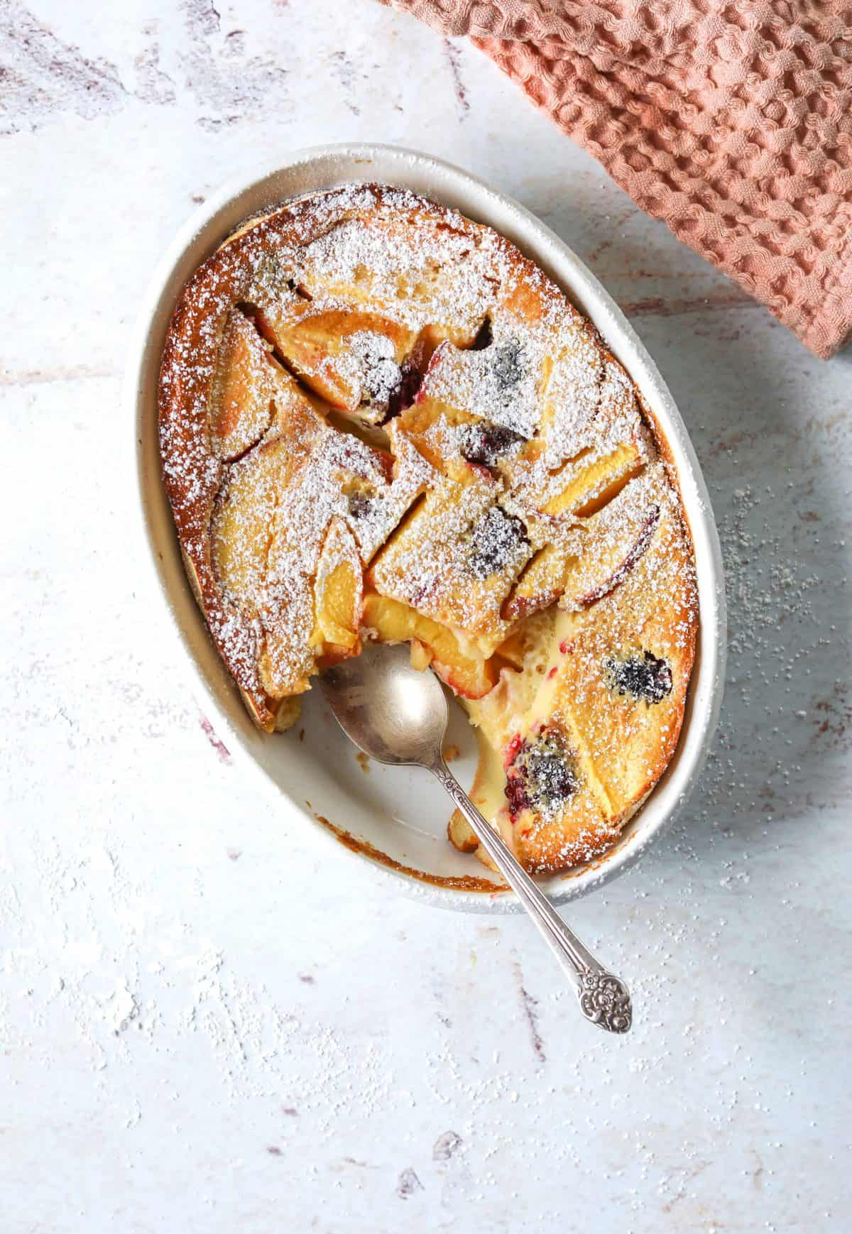 A white oval baking dish filled with Stone Fruit Clafoutis with a silver spoon.