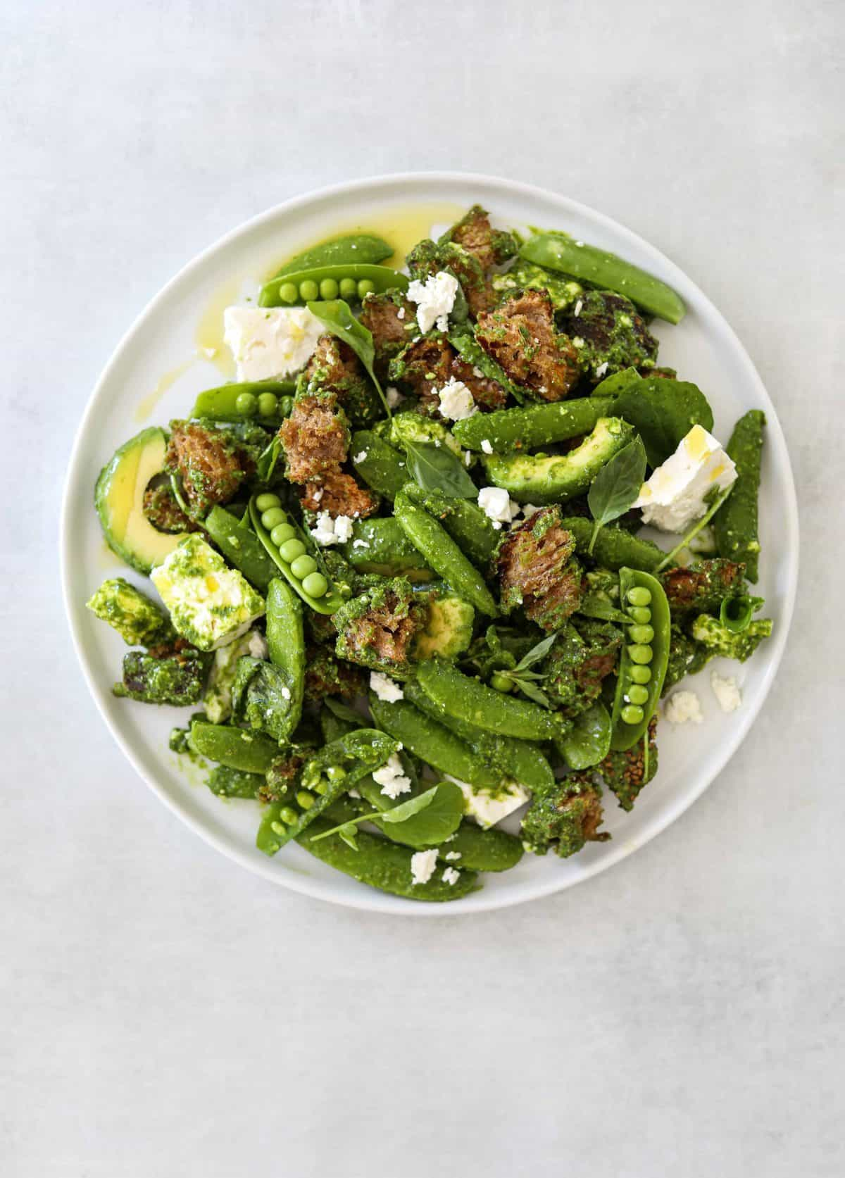 a white plate filled with Avocado Panzanella with Snap Peas + Feta Cheese