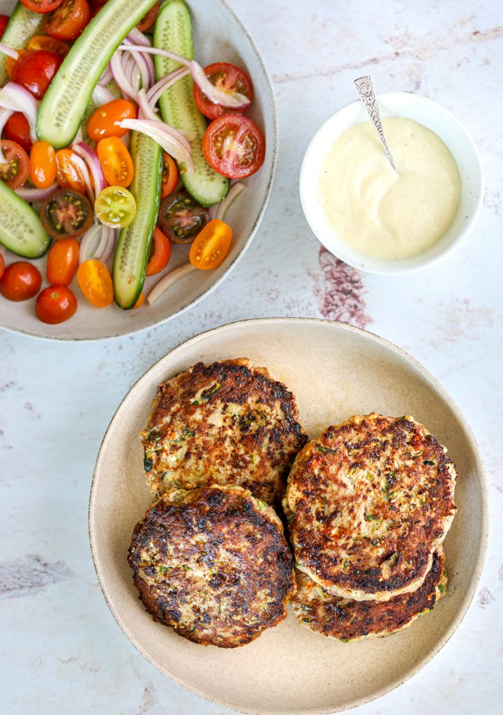 four turkey and zucchini burgers on a plate with a side of tomato and cucumber salad